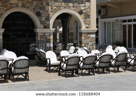 Sunny bar terrace with empty armchairs and tables in Kardamena, Kos, Greece, Europe - stock photo