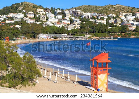 Sunny beach and surfers on calm waves of the Aegean sea, Vouliagmeni, Greece - stock photo