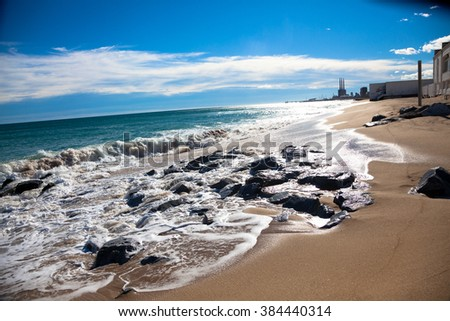 Sunny beach at the day with wet rocks, white clouds and small buildings in the background