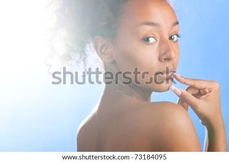 sunny beautiful mulatto woman on sky background - stock photo