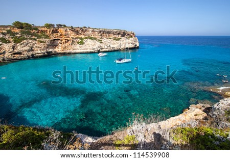 Sunny blue lagoon in Majorca with clear waters - stock photo