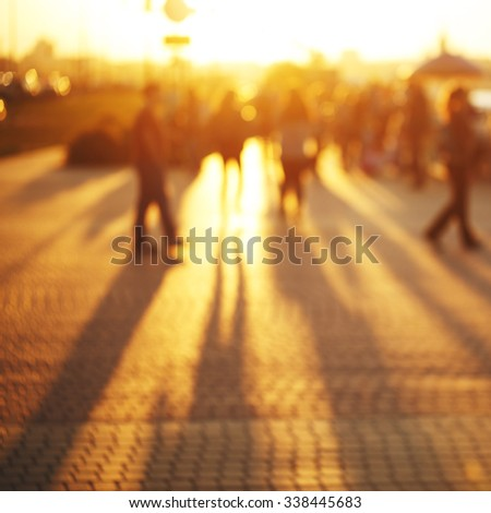 sunny blur summer bright photo of people on street outdoor. Evening yellow sunlight