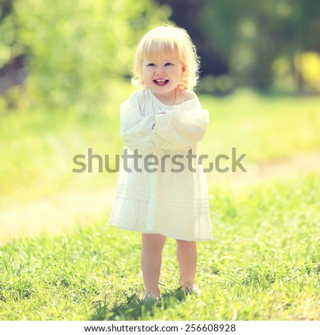 Sunny child having fun on the grass in summer day - stock photo