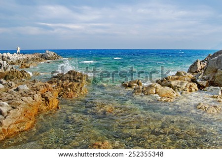 Sunny coastal landscape with rocks, agitated sea and cloudy sky for tourism