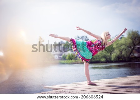 sunny dancing joy: portrait of beautiful blonde young slim woman enjoying stretching posing in long light dress at water lake on summer green outdoors & blue sky copy space background - stock photo