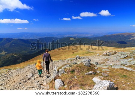Sunny day and a relaxing trip on the mountain for mother and boy - stock photo