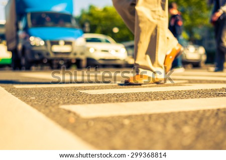 Sunny day in a city, pedestrians crossing the road. View from the level of asphalt, image in the yellow-blue toning - stock photo