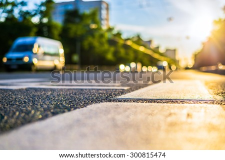 Sunny day in a city, view of the passing cars with level pedestrian crossing - stock photo