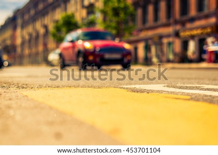 Sunny day in the big city, red car racing on road. View from the pedestrian crossing, focus on the asphalt, image in the yellow-blue toning - stock photo