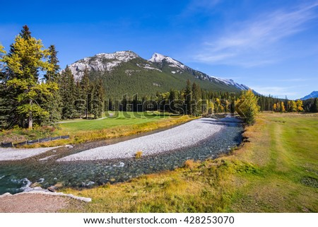 Sunny day in the Rocky Mountains of Canada.  The drying-up stream in the mountain valley park Banff - stock photo