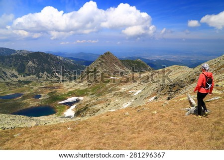 Sunny day of summer with hiker admiring beautiful mountains and lakes from above