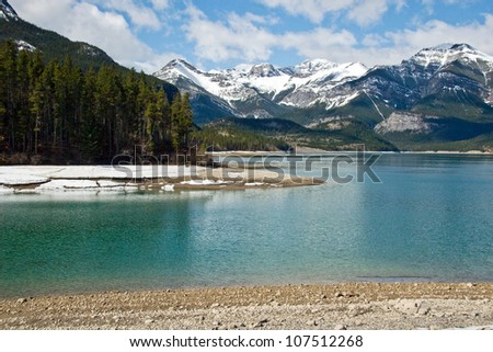 Sunny day on beautiful lake in Canadian Rockies with snow peaks on background - stock photo