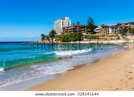 Sunny day on Cronulla beach, Australia. Urban beach with sand shore and buildings with water view. People relaxing on the background. Cronulla, NSW, Australia. - stock photo