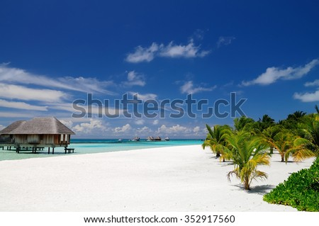 Sunny day on the beach at one tropical resort in Maldives. - stock photo