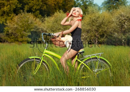 Sunny day, the girl rides a bike on the meadow. - stock photo