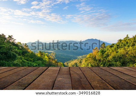 sunny day with landscape and wood terrace - stock photo