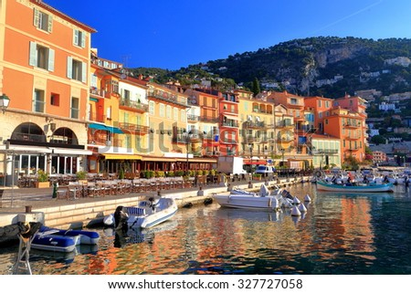 Sunny facades of old buildings along Mediterranean sea in the harbor of Villefranche sur Mer, French Riviera, France