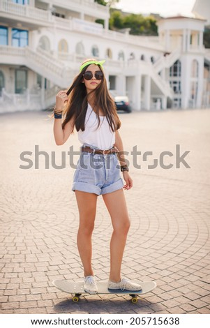 Sunny fashion outdoor urban portrait of pretty brunette fashion woman in city. Beautiful hipster girl with skate board wearing sunglasses. Beautiful and fashion young woman posing with a skateboard
