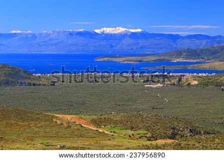 Sunny green fields and snowy mountains across sea, Greece - stock photo