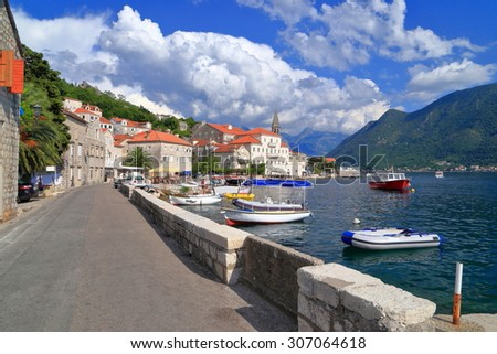Sunny harbor of Perast populated with small boats on the Adriatic sea and surrounded by mountains, Montenegro - stock photo