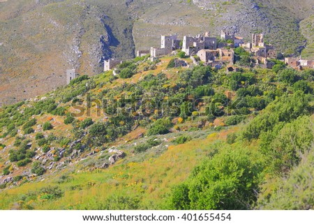 Sunny hillside and distant houses of a Greek village in Vatheia, Greece - stock photo