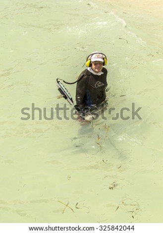SUNNY ISLES BEACH, USA - AUG 17, 2014: man searches with metal detector  for tresuries at the beach in Sunny Isles. Water metal detecting became a famous sport in USA with cheap prices for detectors. - stock photo