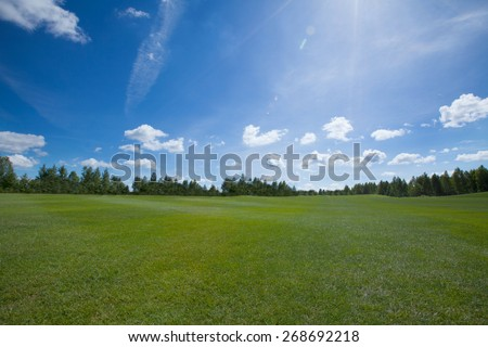 Sunny landmark with grass and blue sky and clouds for background