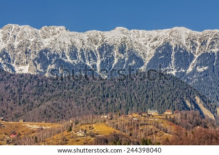 Sunny landscape with remote village in the valley of snowy Piatra Craiului mountains range, Brasov county, Romania. - stock photo