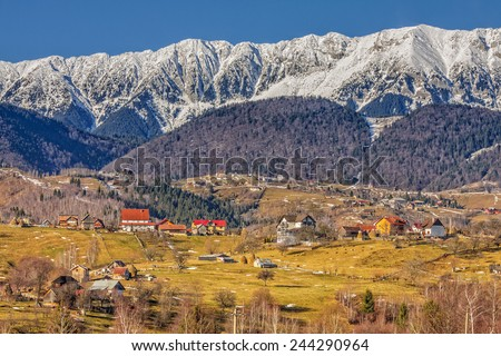 Sunny landscape with small village in the valley of snowy Piatra Craiului mountains range, Brasov county, Romania. - stock photo