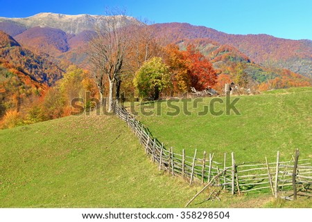 Sunny meadow and traditional wooden fence in front of distant mountains
