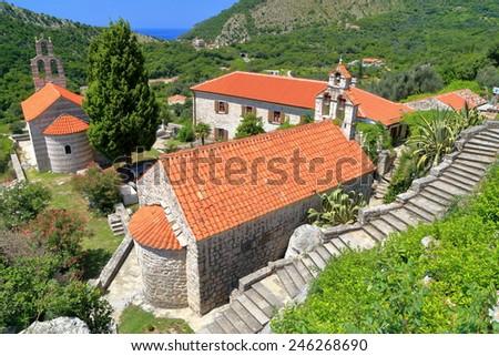 Sunny monastery surrounded green mountains near the Adriatic sea, Montenegro - stock photo