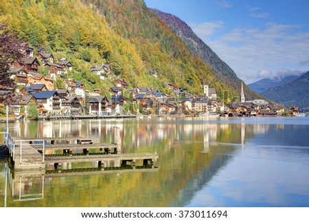 Sunny morning view of Hallstatt with beautiful reflections of a mountainside village on smooth lake water, a charming lakeside village in Salzkammergut region of Austria, in colorful autumn season - stock photo