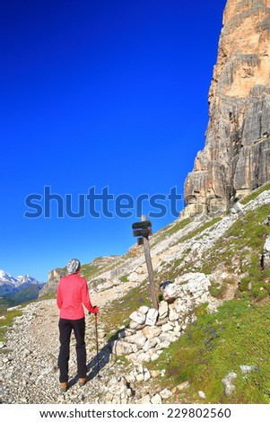 Sunny morning with hiker woman near trail sign, Tofana massif, Dolomite Alps, Italy - stock photo