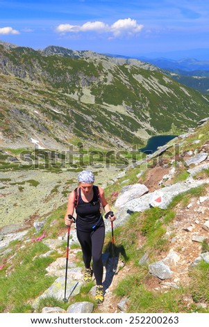 Sunny mountain and hiker woman ascending amongst pink flowers