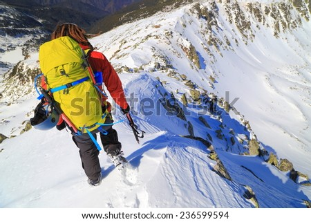 Sunny mountain covered with snow and male climber with a yellow backpack - stock photo