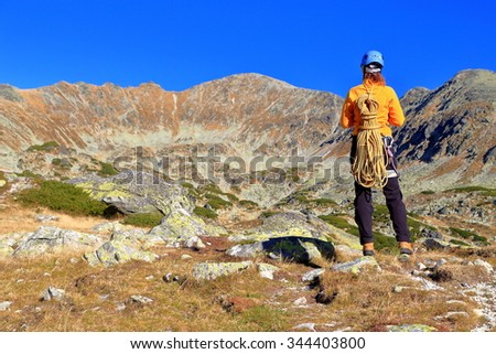 Sunny mountain landscape and climber woman standing and admiring the view - stock photo