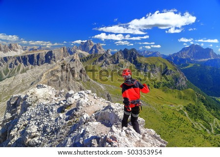 Sunny mountain landscape with climber woman on top of Averau peak, Dolomite Alps, Italy