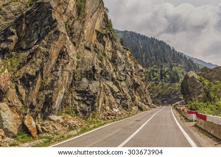 Sunny mountain landscape with Transfagarasan road meandering along high rocky steep cliffs in Fagaras mountains, Romania. - stock photo