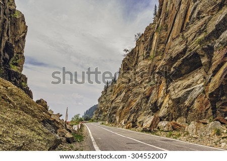 Sunny mountain landscape with Transfagarasan road meandering along high rocky steep cliffs in Fagaras mountains, Romania.