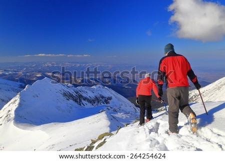 Sunny mountain ridge and a pair of hikers walking on snowy trail in winter - stock photo