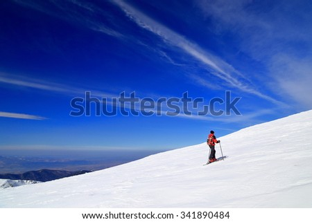 Sunny mountain slope and skier ascending on touring skis in winter - stock photo