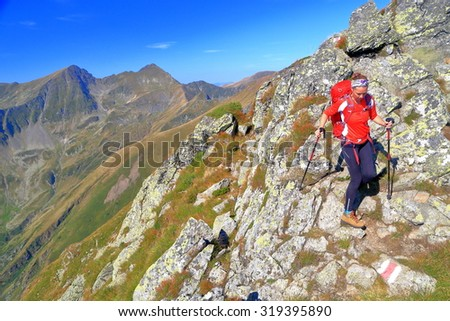 Sunny mountain trail and woman backpacker traversing on the rocks