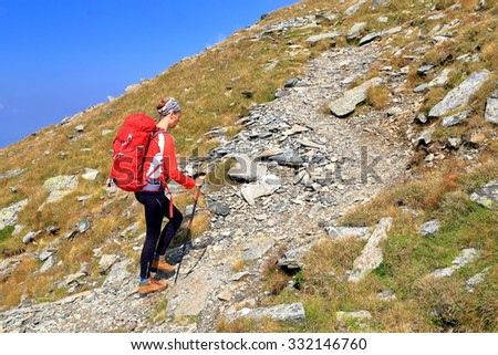Sunny mountain trail and woman walking with a backpack - stock photo