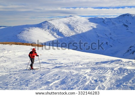 Sunny mountains with ski mountaineer traversing a white slope in winter