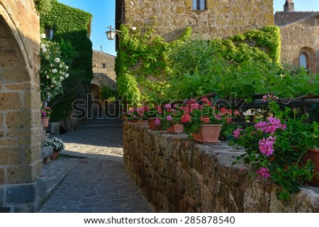 Sunny narrows on a summer day in an old Italian town - stock photo