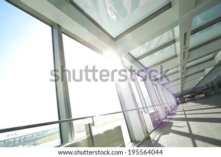 Sunny on modern glass office windows building interior corridor - stock photo