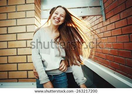 Sunny outdoor portrait of young happy stylish couple having fun. Woman with long hair, laughing. Instagram color style. - stock photo