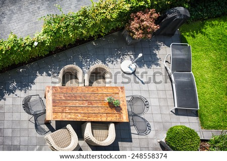 Sunny patio with table and chairs, high angle view - stock photo
