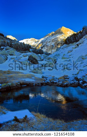 sunny peak reflect on the froze lake - stock photo