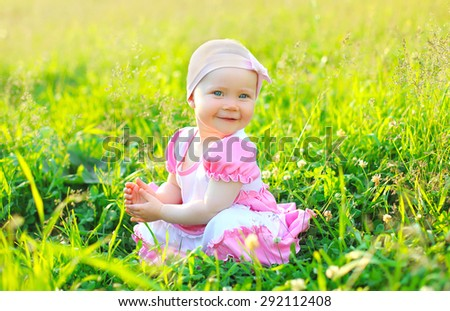 Sunny photo smiling child sitting on the grass in summer day - stock photo